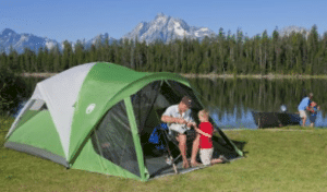 green tent by lake and mountains