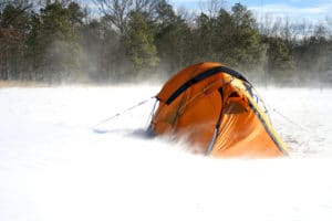 orange tent in winter storm