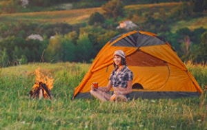 girl camping by camp fire