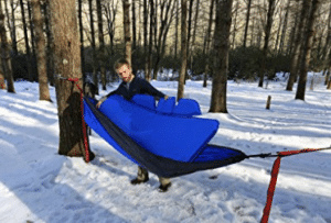 man inserting pad winter camping hammock