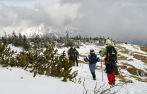 3 winter backpackers trekking thru snow
