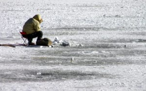 angler ice fishing on lake