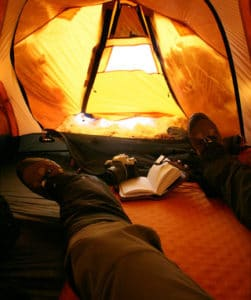 gaitered feet in winter tent with camera and book