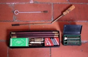 old gun cleaning kit on brick