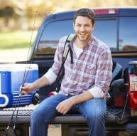 angler sitting on truck bed with cooler