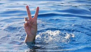 peace sign from hand out of water