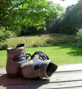 hiking boots on porch overlooking country
