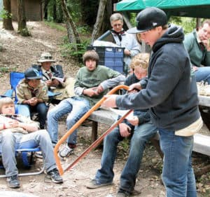 Boy scouts learning about bow saw at camp
