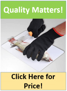 gloved hands filleting fish on cutting board