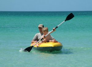 father and son kayaking on beach