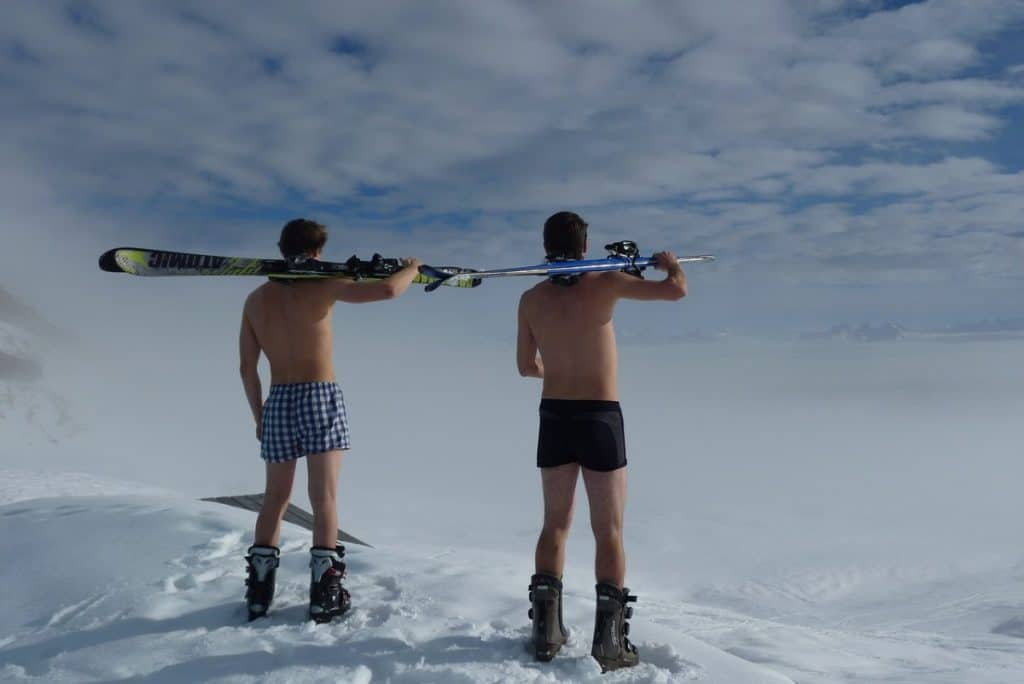 two skiers standing in underwear